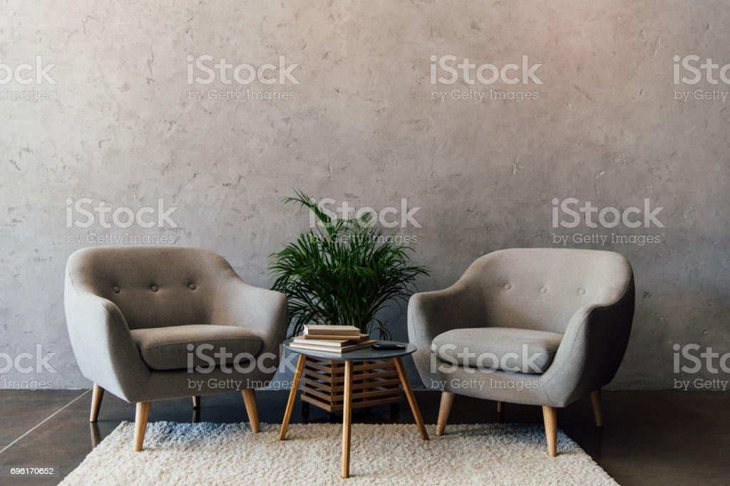 Two cozy grey armchairs standing on white carpet in empty room stock photo