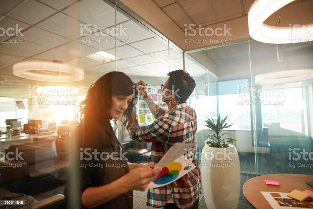 Two creative professionals working on new project. Woman looking at...