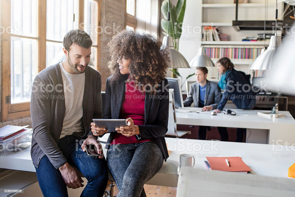 Two creatives checking a project in the digital tablet stock photo