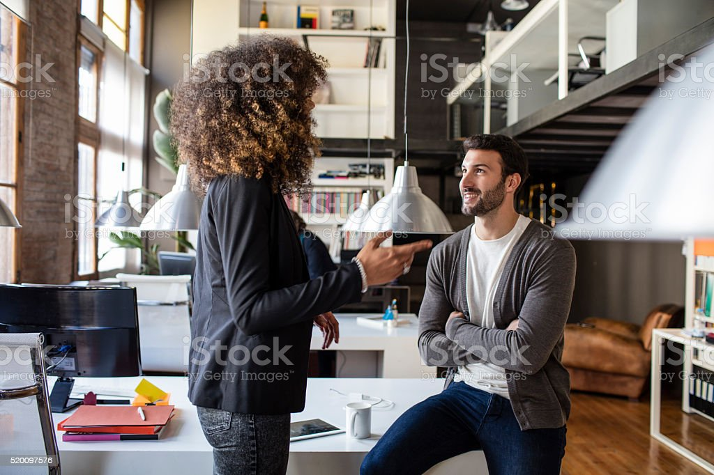 Two creatives talking in the office stock photo