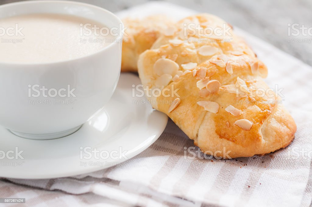 Two croissant with almonds and cup of cappuccino stock photo