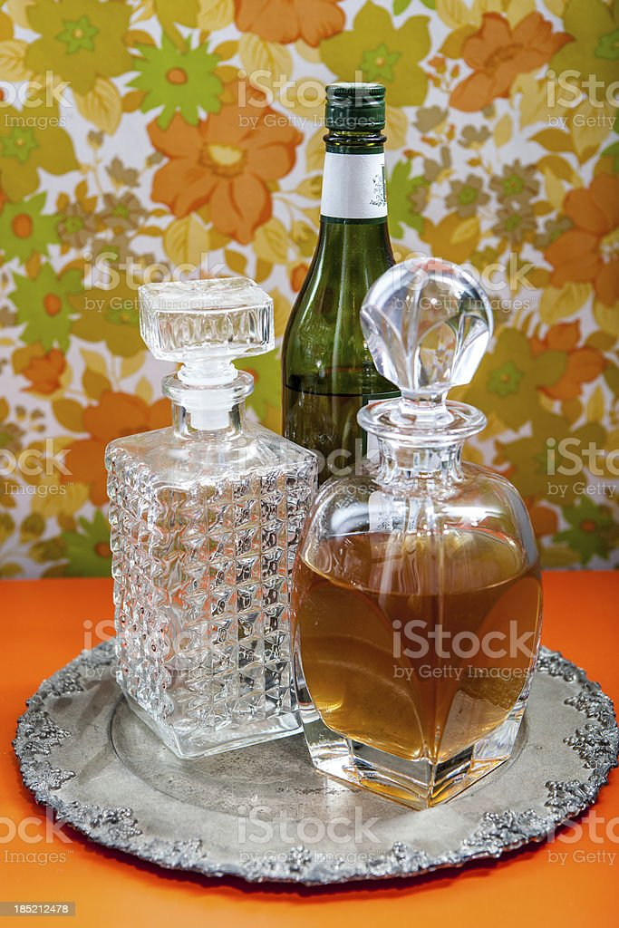 Two Crystal Decanters on a Silver Plate with Wine Bottle royalty-free stock photo
