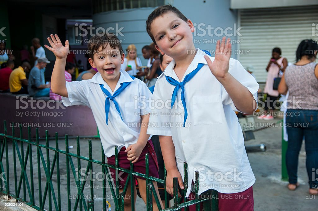 Two Cuban school kids in uniform excitedly wave stock photo