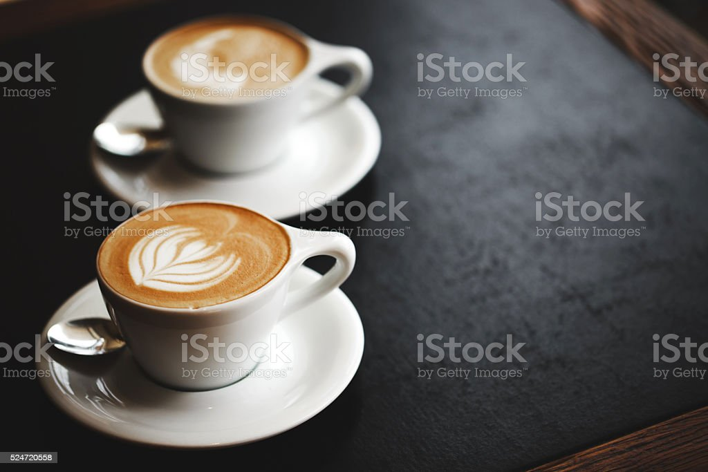 Two cups of cappuccino on black table stock photo
