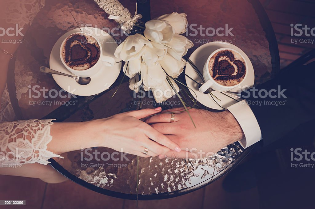 Two cups of coffee and hand of bride and groom stock photo
