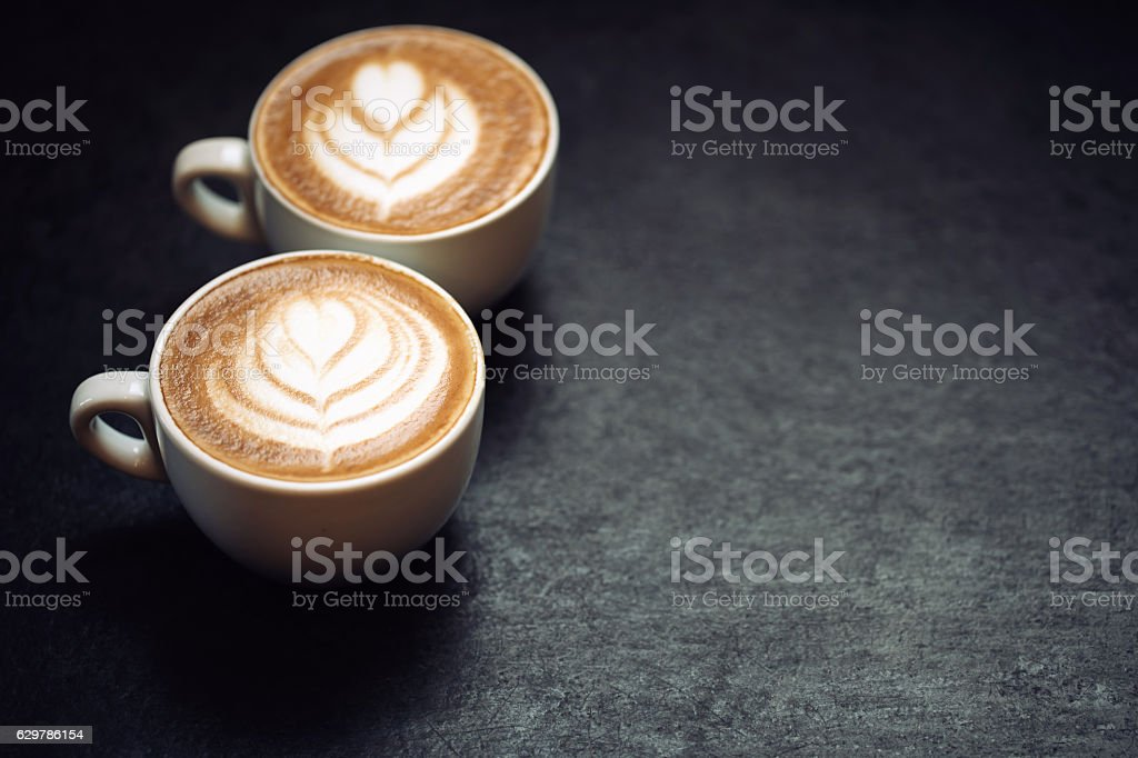 Two cups of coffee on black rustic background stock photo