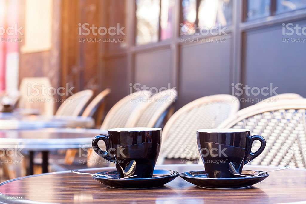 Two cups of coffee on restaurant terrace with afternoon sunlight stock photo