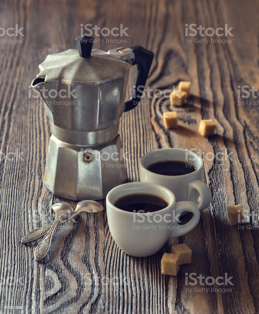 Two cups of coffee with pieces of cane sugar and Italian  coffee maker on wooden table.  Toned image. stock photo