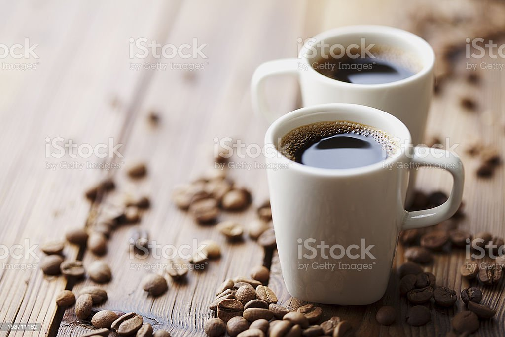 Two cups of expresso surrounded by coffee beans stock photo