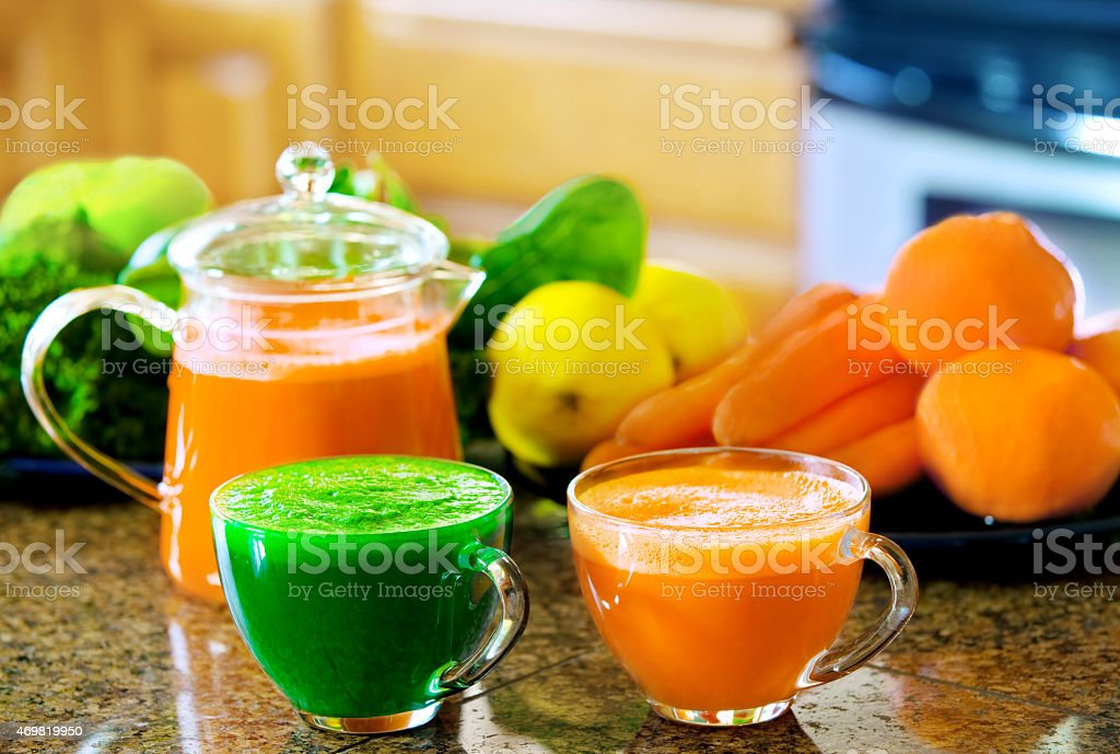 Two cups of fresh vegetable juice on counter with vegetables stock photo