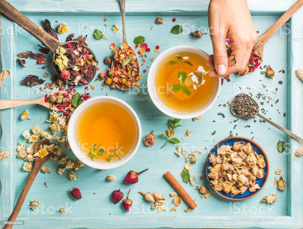 Two cups of healthy herbal tea with mint, cinnamon, dried rose, camomile flowers in spoons and man's hand holding spoon stock photo
