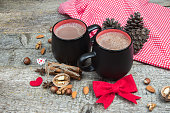 Two cups of hot chocolate and Christmas decorations. Wooden background