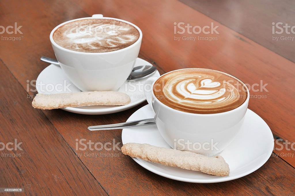 two cups of latte art coffee in a white cup stock photo