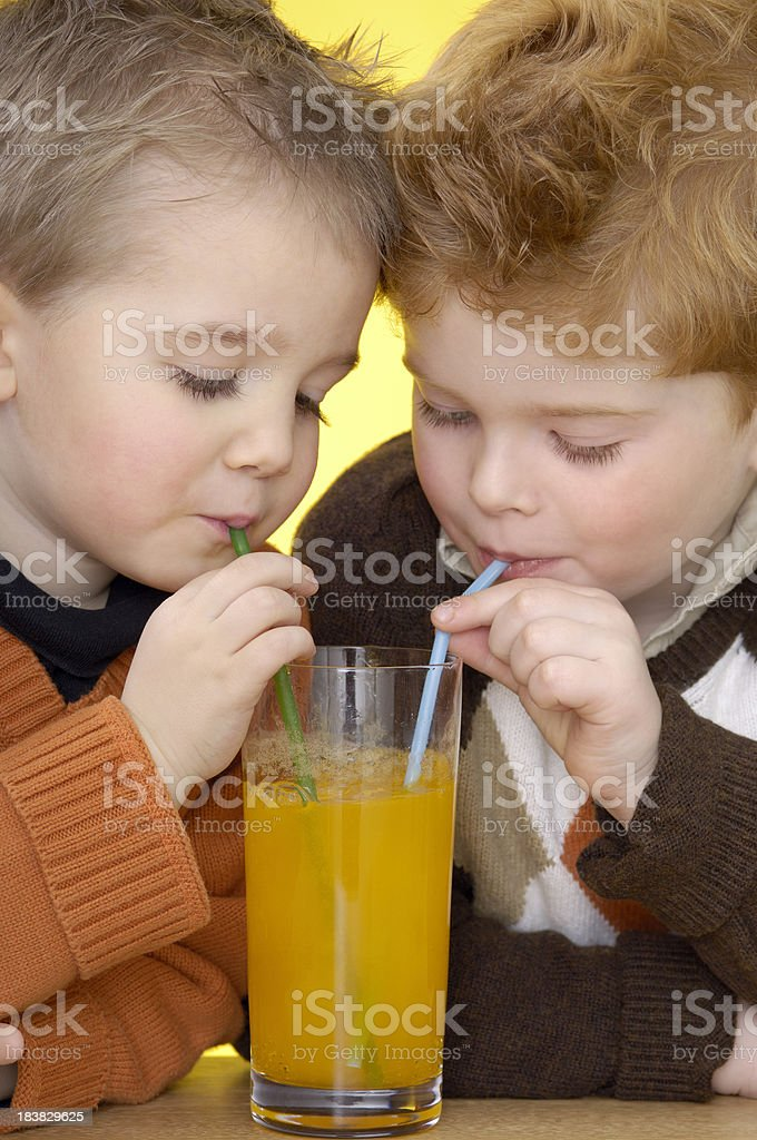 Two cute boys are drinking orange lemonade royalty-free stock photo