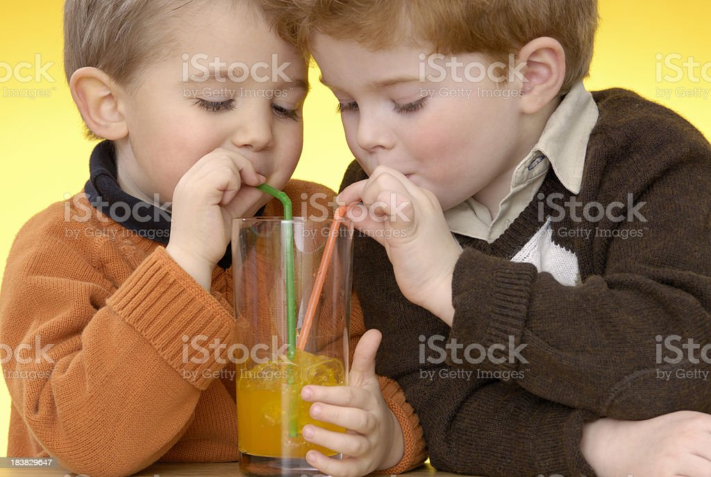 Two cute boys are making bubbles with orange lemonade royalty-free stock photo