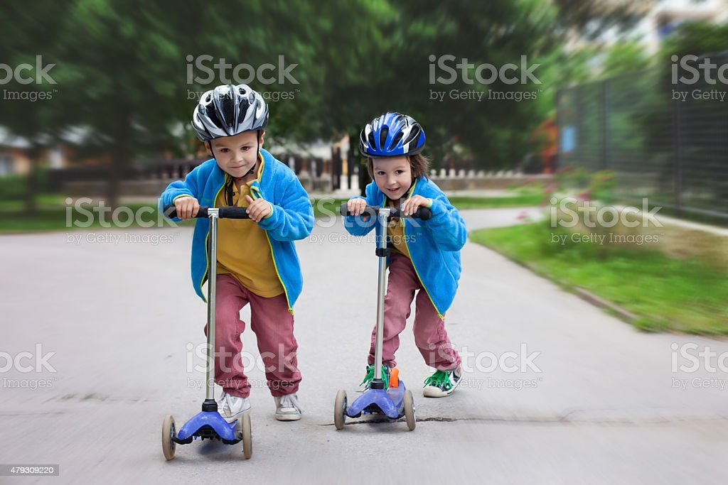 Two cute boys, compete in riding scooters, outdoors stock photo