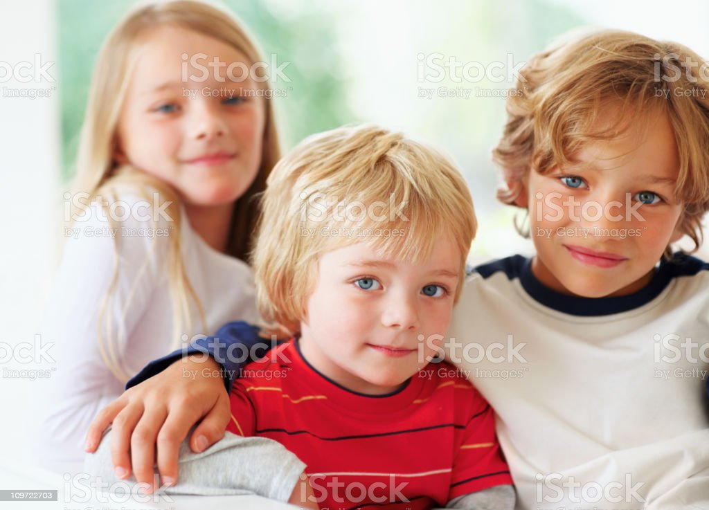 Two cute brothers and a sister sitting together royalty-free stock photo