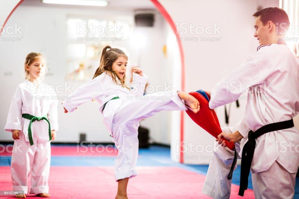 Two cute girls on taekwondo training, kicking and learning self-defence stock photo