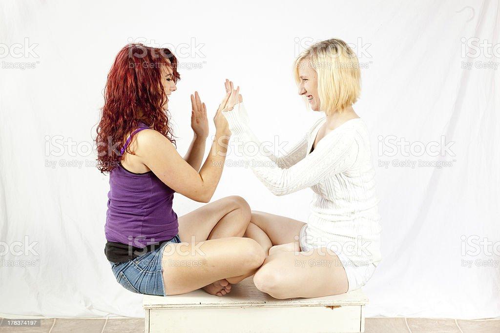 Two cute girls playing patty cake stock photo