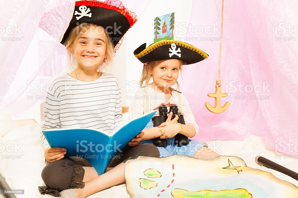 Two cute girls playing pirates, reading fairy-tale stock photo