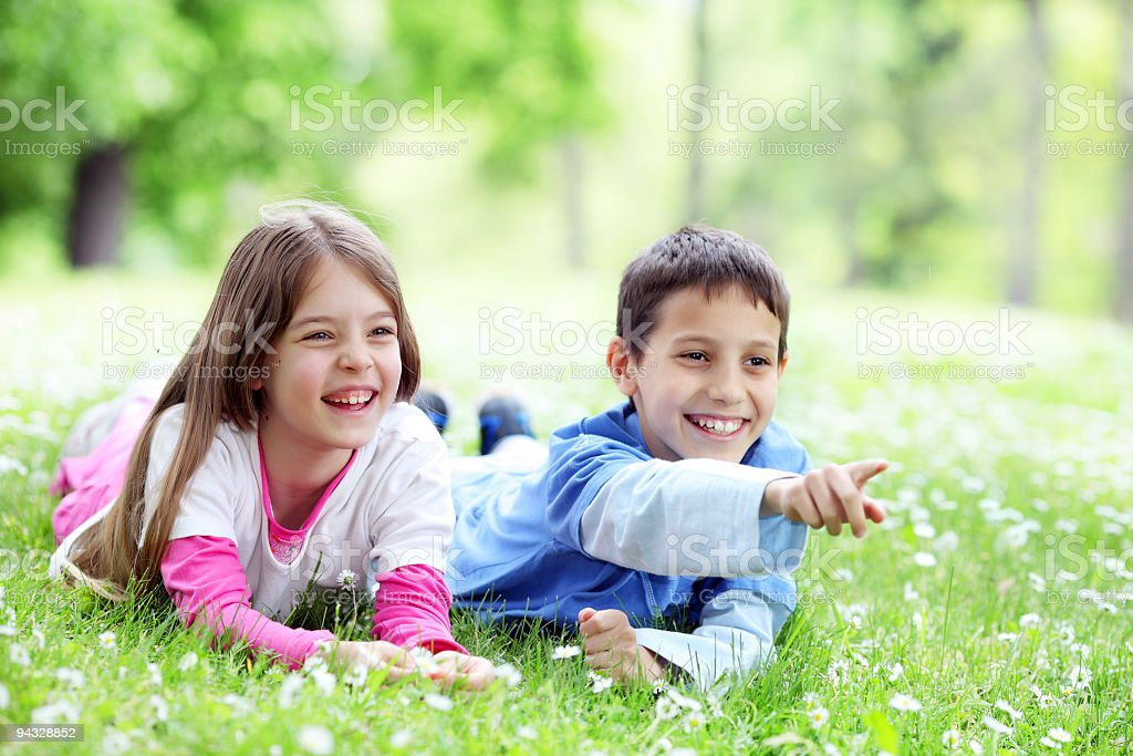 Two cute laughing children resting on park royalty-free stock photo