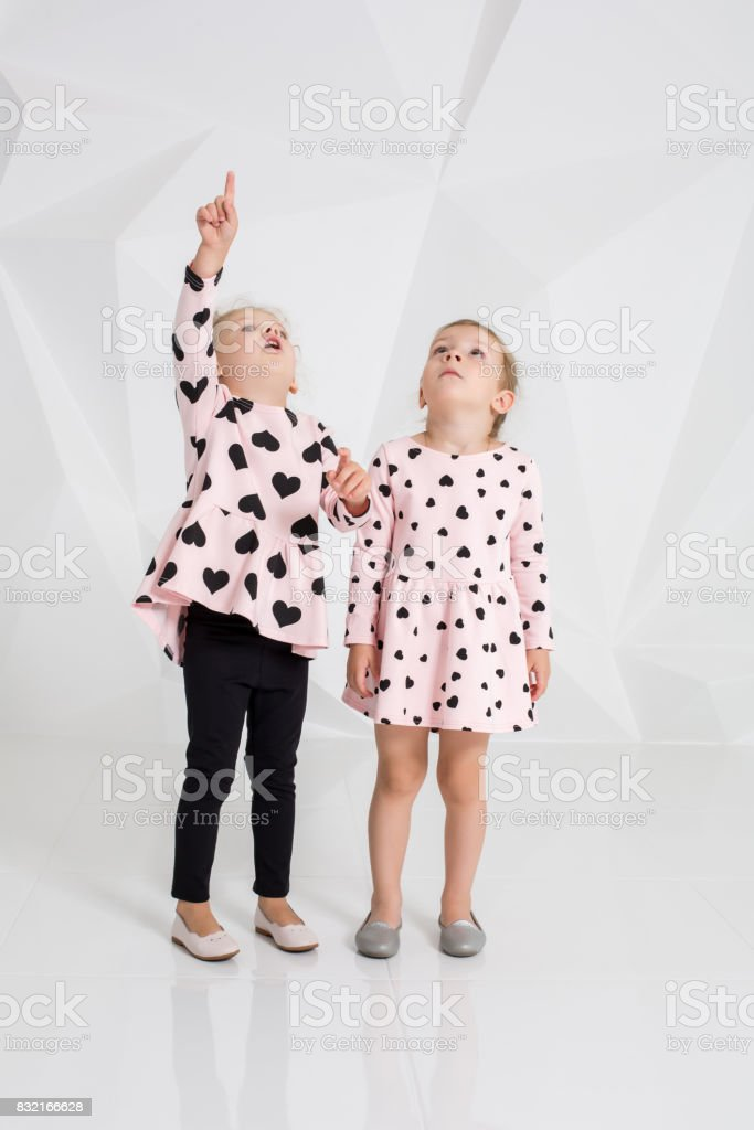 Two cute little girls standing in pink clothes with black hearts on the white wall background in the studio stock photo