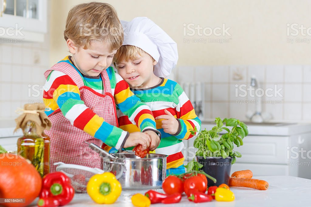 Two cute little kid boys cooking with vegetables stock photo