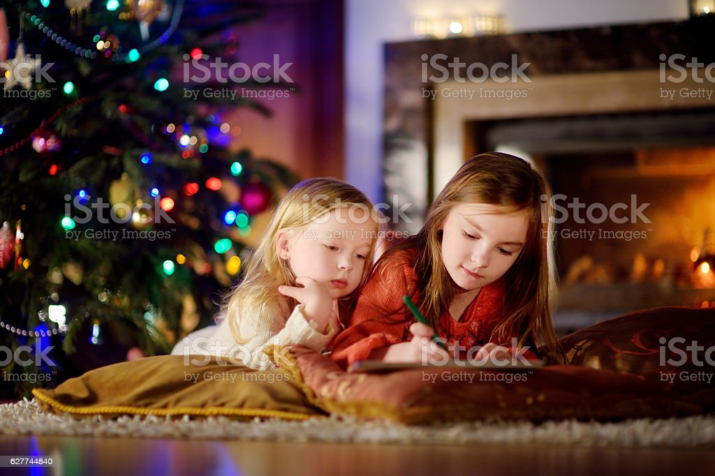 Two cute little sisters writing letter to Santa on Christmas stock photo