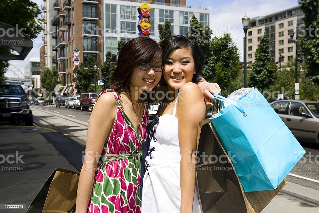 Asian Young Women Hugging with Shopping Bags Downtown royalty-free stock photo