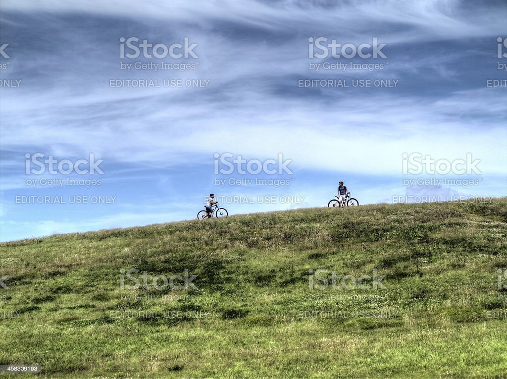 Two cyclists above grassy gnoll royalty-free stock photo