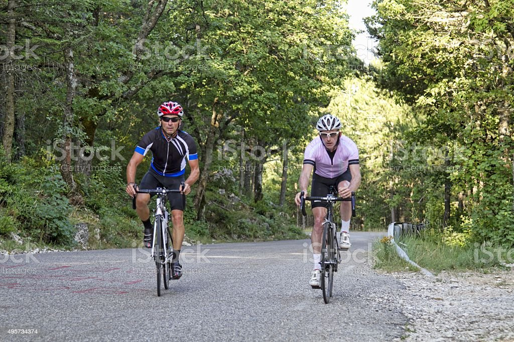 Two cyclists ascending a steep hill stock photo