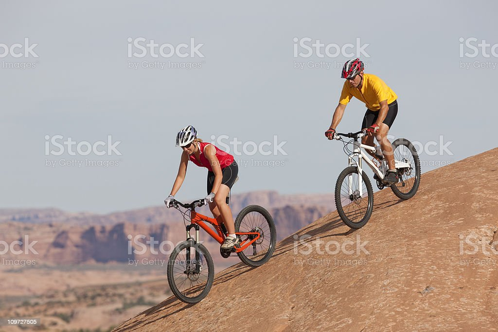 Two Cyclists Going Downhill On Mountain Bikes In Moab, Utah royalty-free stock photo