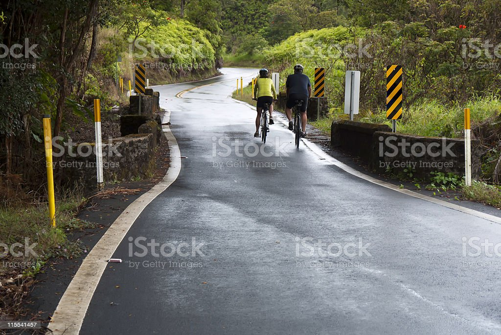 Two cyclists on rain dampened rural road royalty-free stock photo