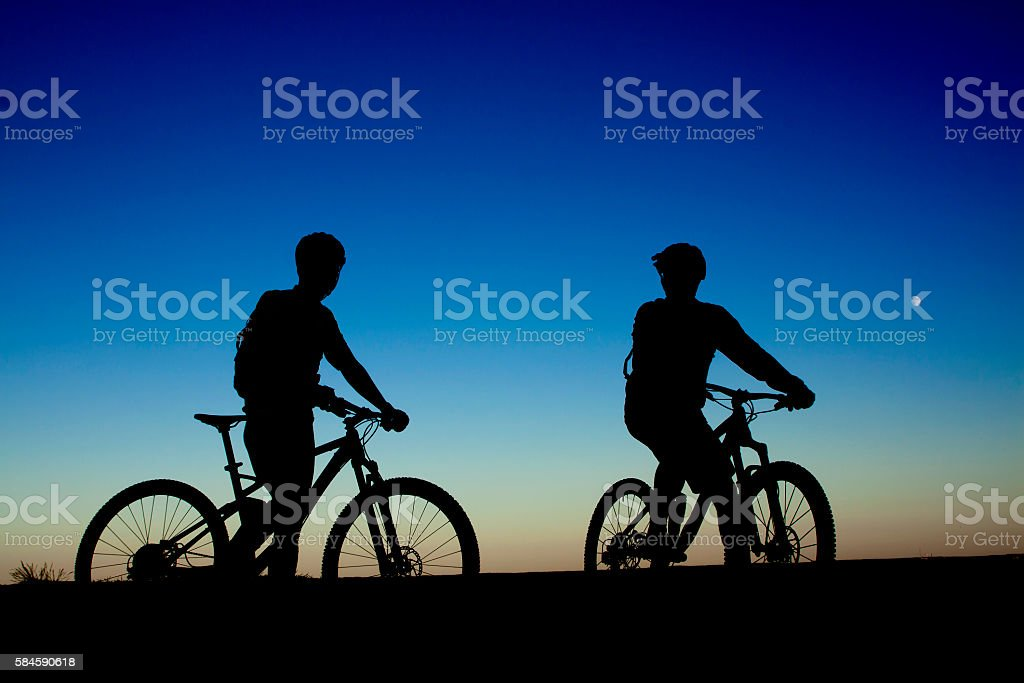 Two cyclists on the background of night sky stock photo