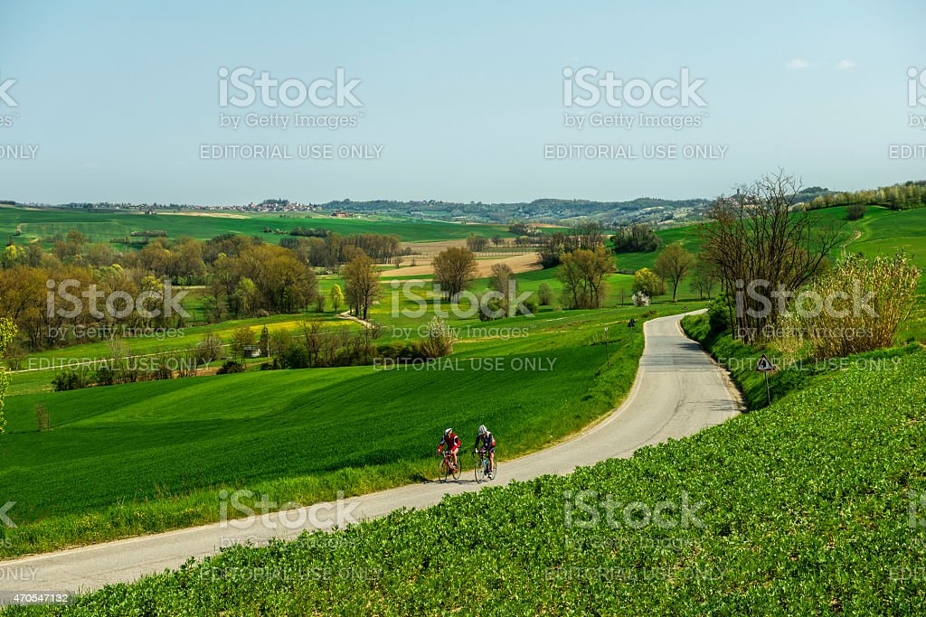Two cyclists riding on a beautiful road amid green hills stock photo