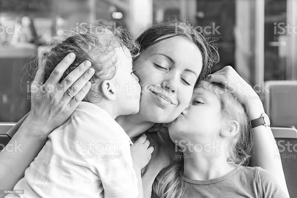 Two daughters kissing their happy mother stock photo