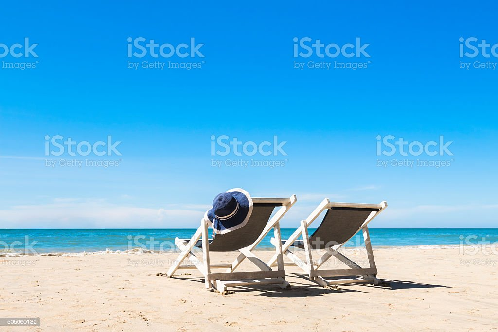 Two deck chairs and hat, relaxing on the beach, sunny stock photo