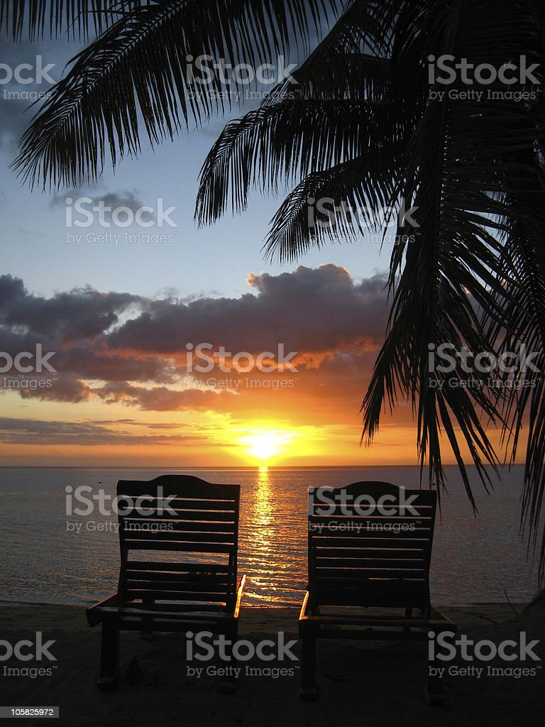 Two deckchairs on beach at sunset royalty-free stock photo