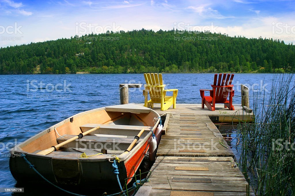 Two deckchairs on the end of a wooden pier on a lake stock photo