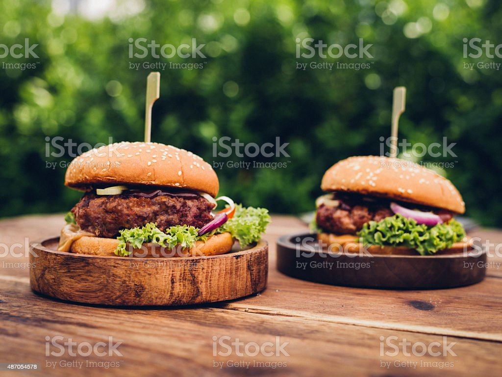 Two delicious gourmet beef burgers on wooden platters outdoors stock photo