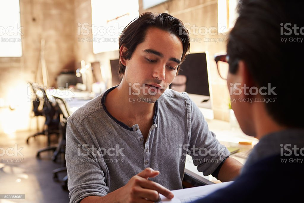Two Designers Discuss Document During Meeting In Office stock photo