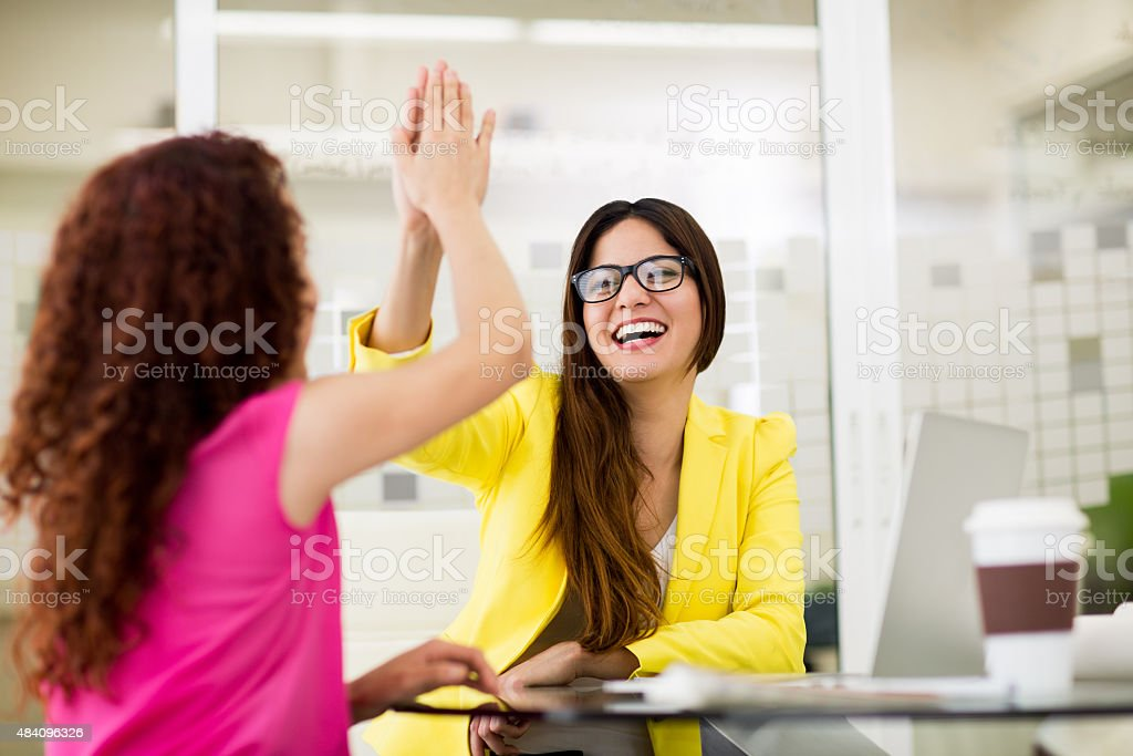 Two designers giving high five to each other stock photo
