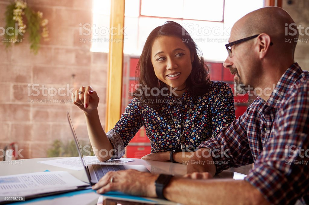 Two Designers With Laptop Meeting In Modern Office stock photo