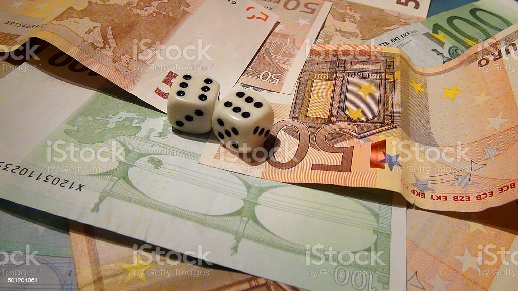 Two dices on a pile of euro bills stock photo