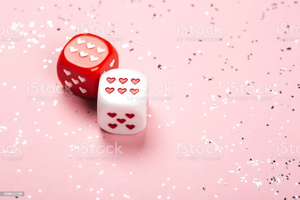 Two dices with hearts on pink background stock photo