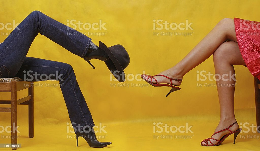 two different dressed women, sitting one against another stock photo