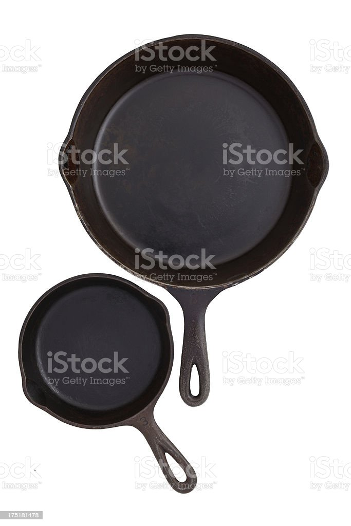 Two different sized black cast iron skillets on white background. stock photo