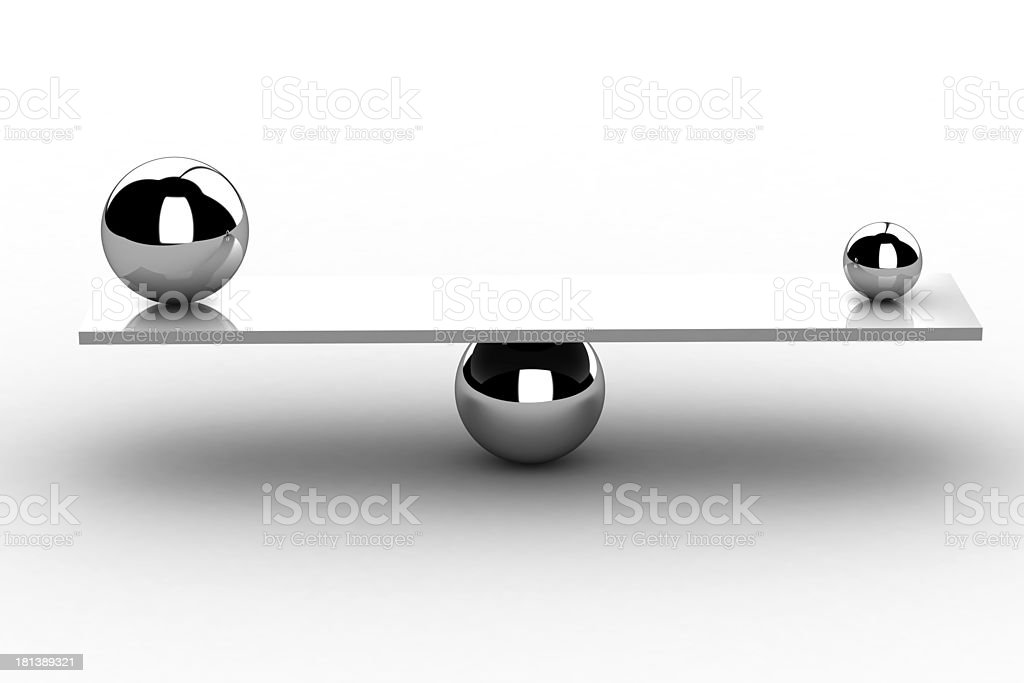 Two different sized, silver balls balancing on a board stock photo