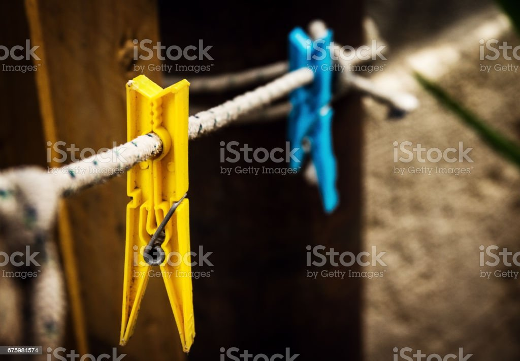 Two different wash pins yellow and blue hanging on rope on vintage background. stock photo