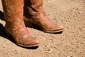 Two dirty western cowboy boots standing on dirt ground